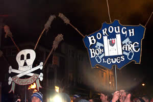 Two of Lewes Borough Bonfire Society's banners being carried in procession, the torches still unlit